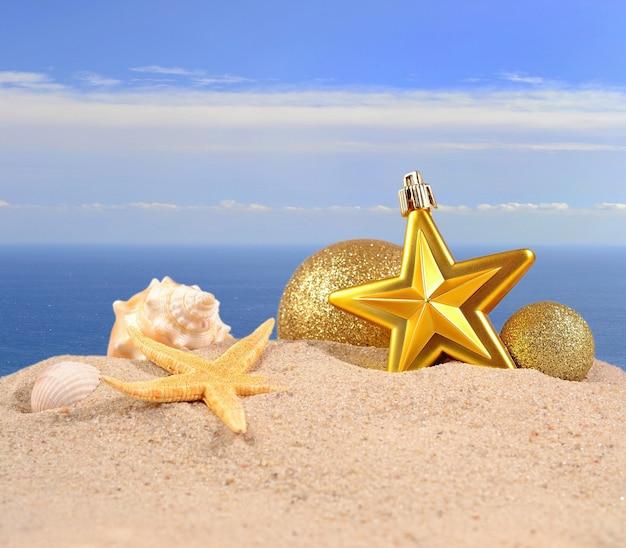 Рождественские украшения, ракушки и морские звезды на песчаном пляже на фоне моря