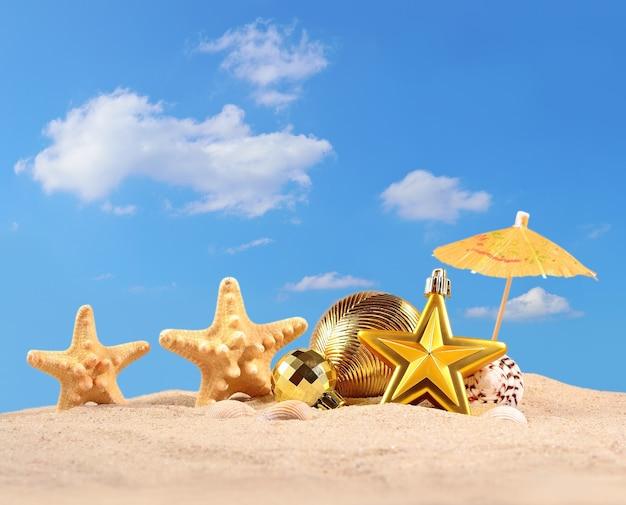 Рождественские украшения, ракушки и морские звезды на песчаном пляже на фоне голубого неба