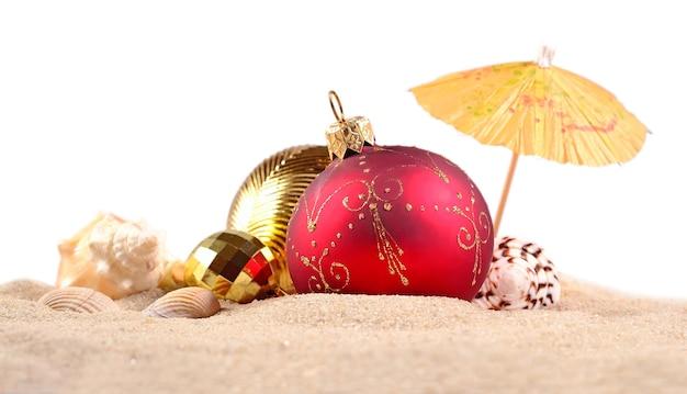 Рождественские украшения ракушки и морские звезды на песке пляжа на белом фоне