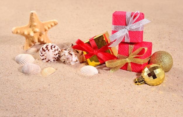 Рождественские украшения, ракушки и морские звезды на песке пляжа