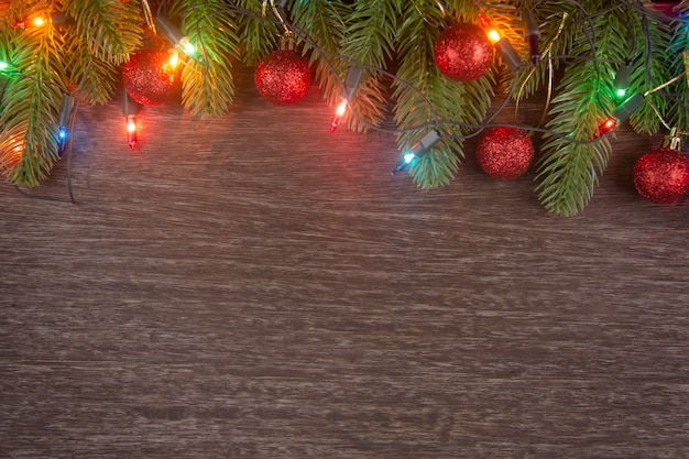 Christmas decorations with branches of fir tree christmas lights ball and pine cones on wooden