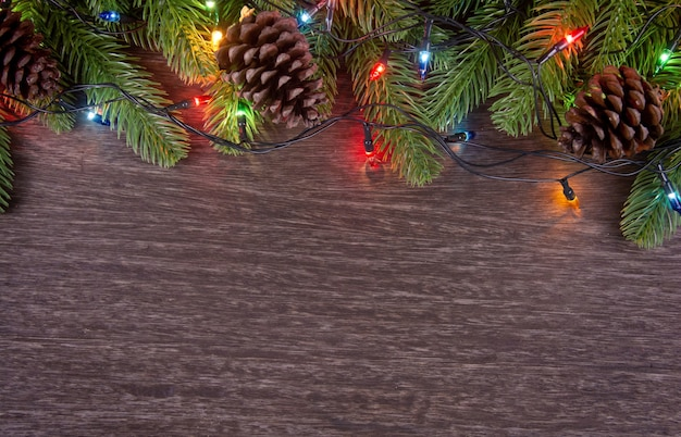 Christmas decorations with branches of fir tree christmas lights ball and pine on wooden