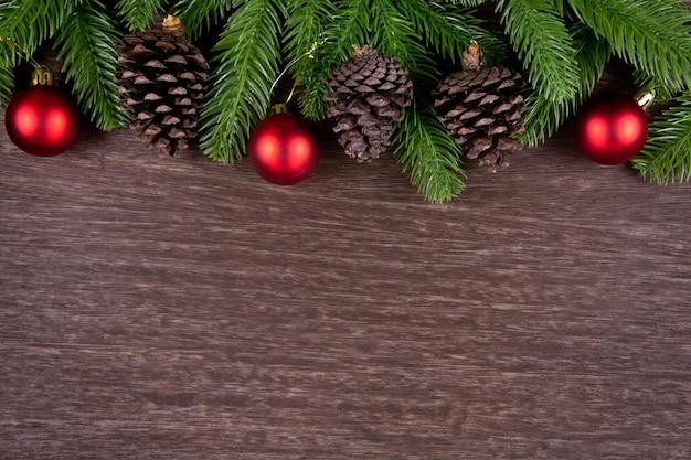 나무 배경에 전나무 크리스마스 공과 소나무 가지가 있는 크리스마스 장식
