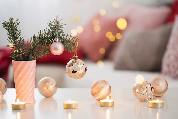 ピンクとゴールドのコロで燃えるろうそくとクリスマスの装飾