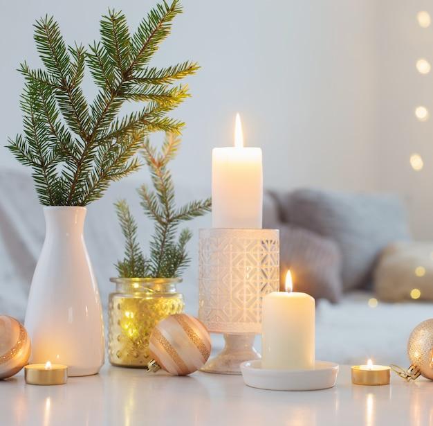 Рождественские украшения с зажженными свечами в белом интерьере