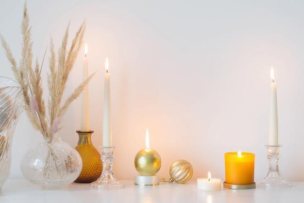 흰색 방에 촛불을 태우는 크리스마스 장식