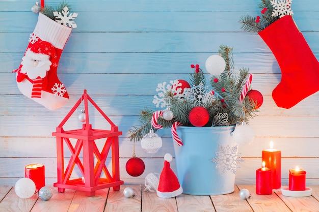 Рождественские украшения с зажженными свечами на синем деревянном фоне