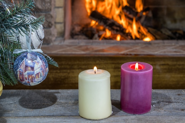 Christmas decorations with candles before cozy fireplace in country house.