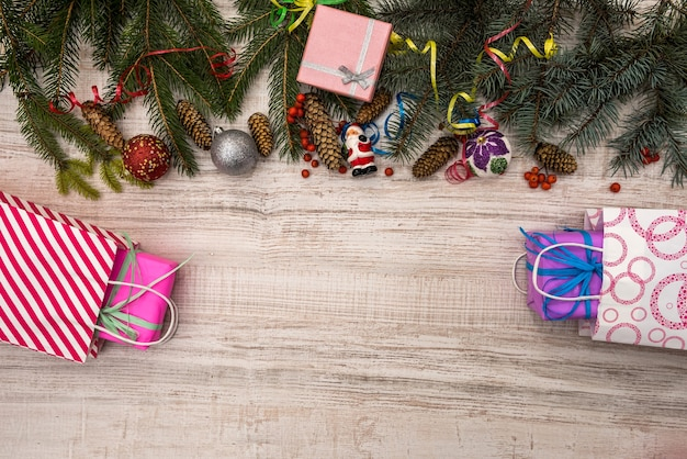 Christmas decorations with fir branches on wooden table. gift boxes with ribbons. presents concept
