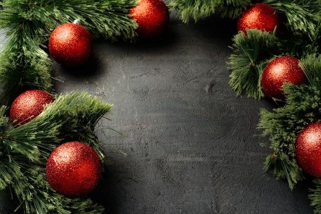 전나무 나무 가지와 블랙에 빨간 싸구려 크리스마스 장식 프리미엄 사진