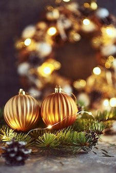 Christmas decorations with golden balls, fir tree branch and garland lights on a dark