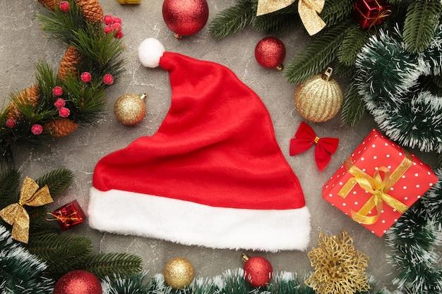 灰色の背景にサンタの帽子とクリスマスの装飾。上面図