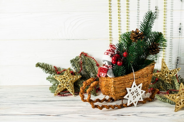 Christmas decorations with sled, penguin, pinecones, green spuce tree branches and gold decorative stars. greetings card with copyspace for your text