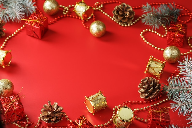 여유 공간이 빨간색 배경에 가문비 나무 가지와 크리스마스 장식. 연말 연시와 크리스마스