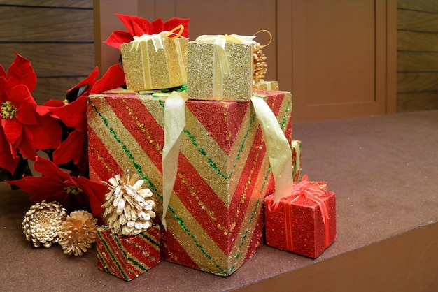 Christmas decorations with stack of big and small gift boxes and dry pine cones on the floor