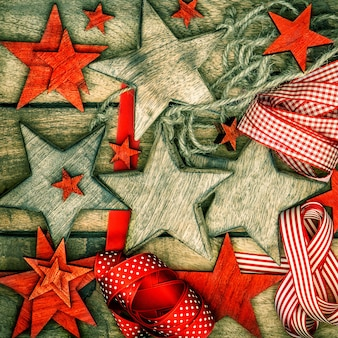 Christmas decorations wooden stars and red ribbons. nostalgic retro style picture. dark designed photo