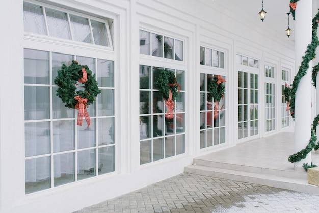 Елочные игрушки: венки с бантами на белых французских окнах частного дома.