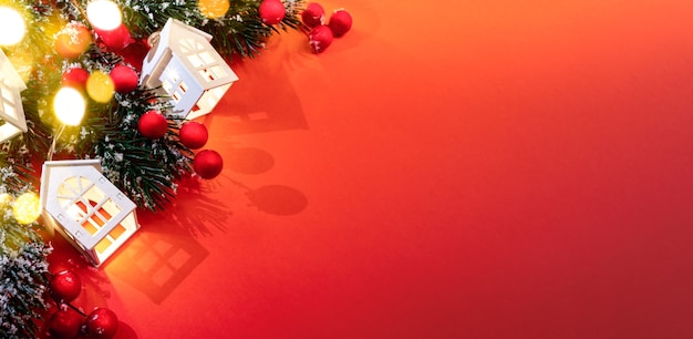 Рождественские украшения: ветки рождественской елки, светящиеся рождественские огни, белые домики, красные ягоды, сверкающие огни боке на красном