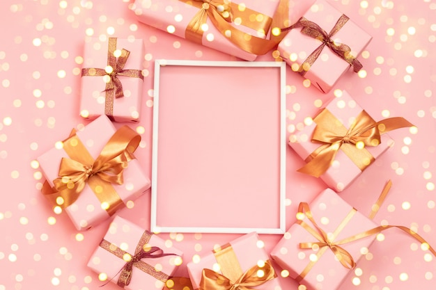 Christmas decorative composition frame with paper pink present boxes, gold bow and confetti on grey background.