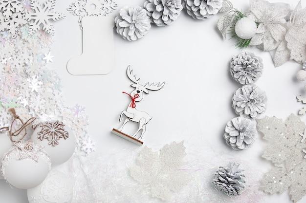 白いテーブルの背景におもちゃのクリスマス装飾的な組成物。上面図。フラットレイ