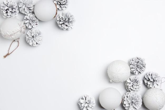 白い壁のシュルレアリスムのおもちゃのクリスマスの装飾的な構成。上面図