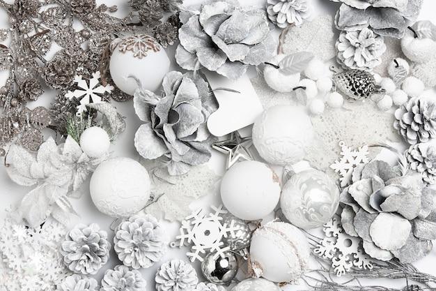 Новогодняя декоративная композиция из игрушек на белой стене сюрреализм. вид сверху