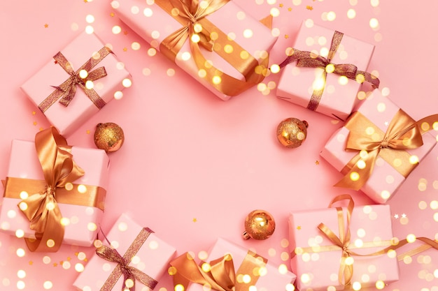 Christmas decorative composition with paper gift box, gold christmas balls and gold ribbon bow on a pink background.