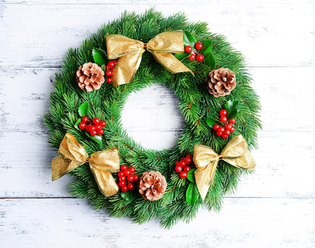 Christmas decorative wreath with leafs of mistletoe on wooden surface