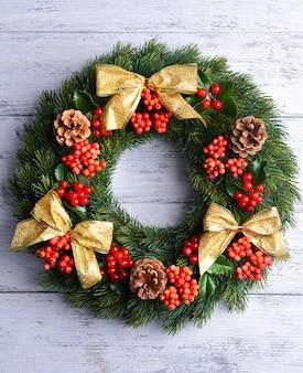 Рождественский декоративный венок с листьями омелы на деревянном фоне