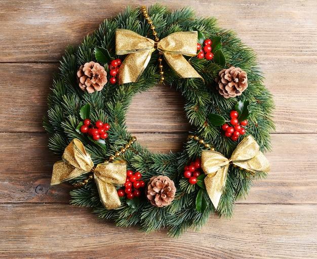 木製の表面にヤドリギの葉を持つクリスマスの装飾的な花輪