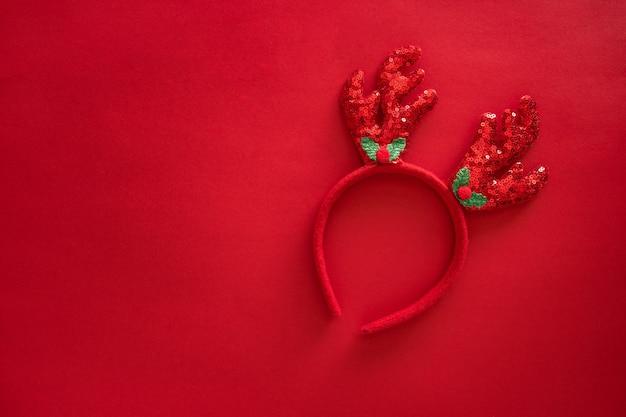赤い表面に流行に敏感なスタイルのクリスマスの鹿の角。カラフルなトナカイの角のヘッドバンド。ホリデーコスチュームの詳細。コピースペース、上面図