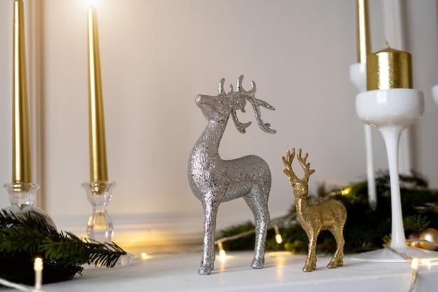 Рождественские олени стоят под елкой.
