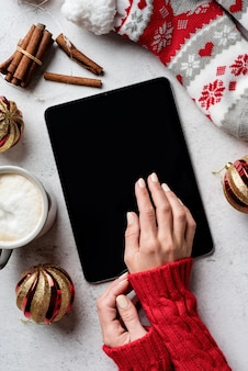 Christmas desktop with woman hands tablet