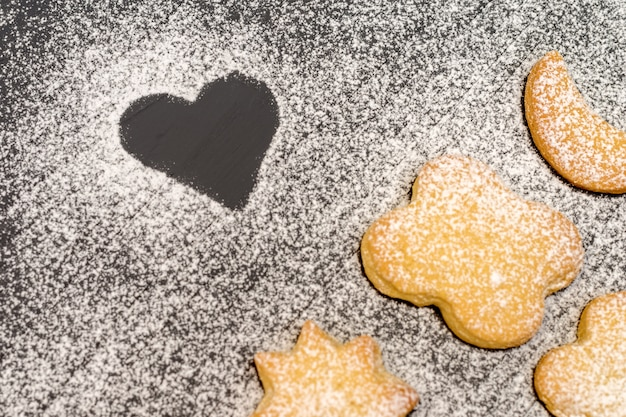 Christmas different shaped cookies with sugar powder on dark wooden table