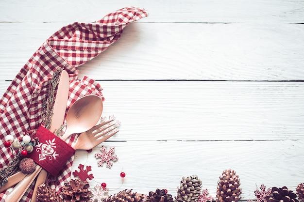白い木製の背景に装飾が施されたクリスマスディナーの美しいカトラリー