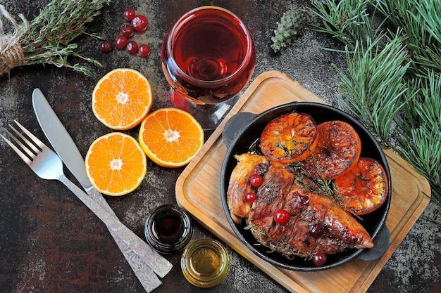 Рождественский ужин. куриная грудка, запеченная с мандаринами и клюквой. рождественская елка ветви и бокал вина.