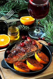 Christmas dinner. chicken breast baked with tangerines and cranberries. christmas tree branches and a glass of wine.