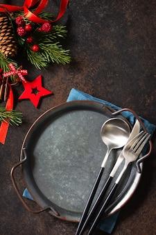 クリスマスディナーのコンセプト、料理の背景。石のカウンタートップに金属板、カトラリー、ナプキン。石のカウンタートップのテーブルセッティング。コピースペースのある上面図フラットレイ背景。