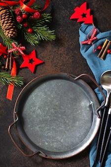 クリスマスディナーのコンセプト、料理の背景。石のカウンタートップに金属板、カトラリー、ナプキン。石のカウンタートップのテーブルセッティング。フラットレイの上面図。 Premium写真