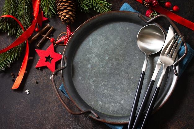 クリスマスディナーのコンセプト、料理の背景。石のカウンタートップに金属板、カトラリー、ナプキン。石のカウンタートップのテーブルセッティング。