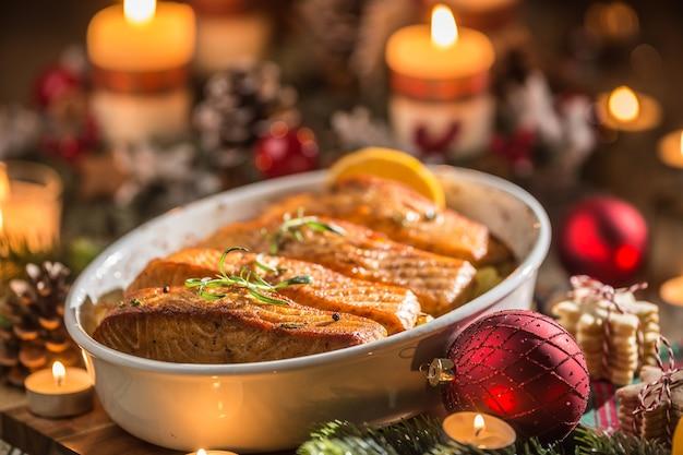 축제 장식 출현 화환과 불타는 초와 함께 구운 접시에 생선 연어에서 크리스마스 저녁 식사.