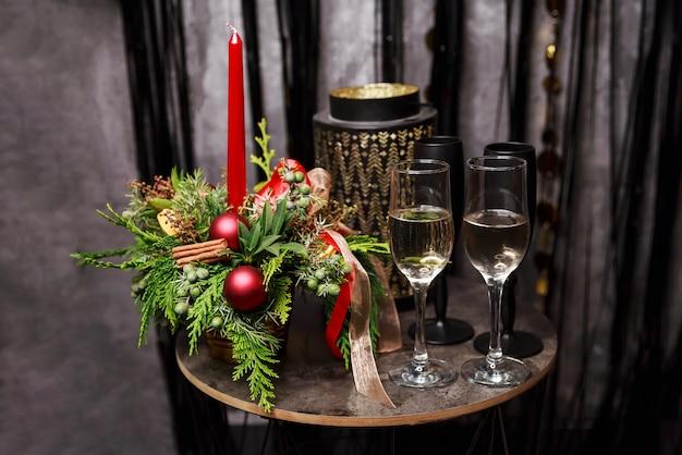 Рождественский обед изображение. стол с двумя фужерами. вечерние огни и свечи в интерьере ресторана. романтический ужин, ночь свиданий. сервировка праздничного стола. напитки и бокал для вина. канун нового года.