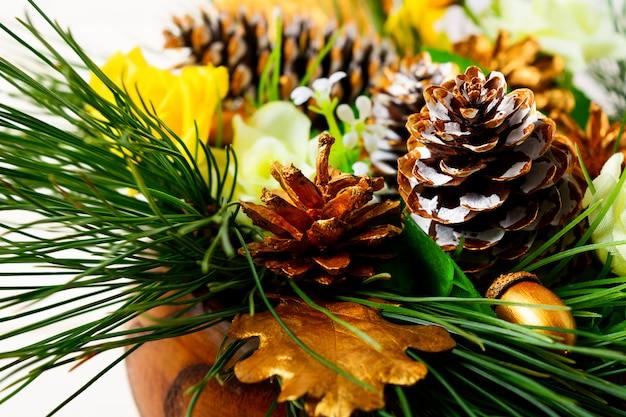 Украшение стола для рождественского ужина с сосновыми ветками и золотыми шишками