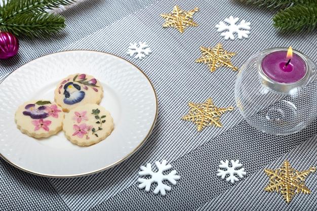 美しい食用フラワークッキーと香りのキャンドルでクリスマスディナーテーブルの装飾。