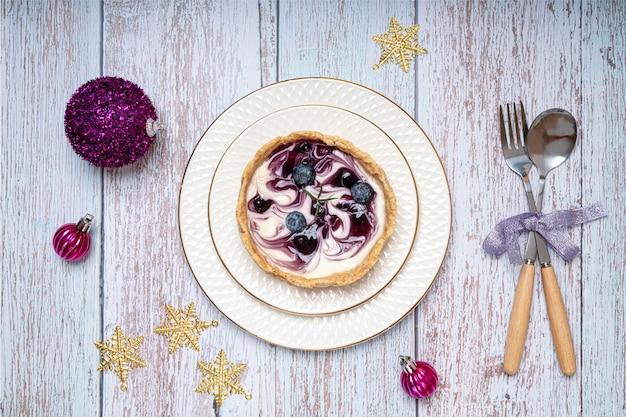 白い磁器のプレートにブルーベリーチーズケーキとクリスマスディナーテーブルの装飾。