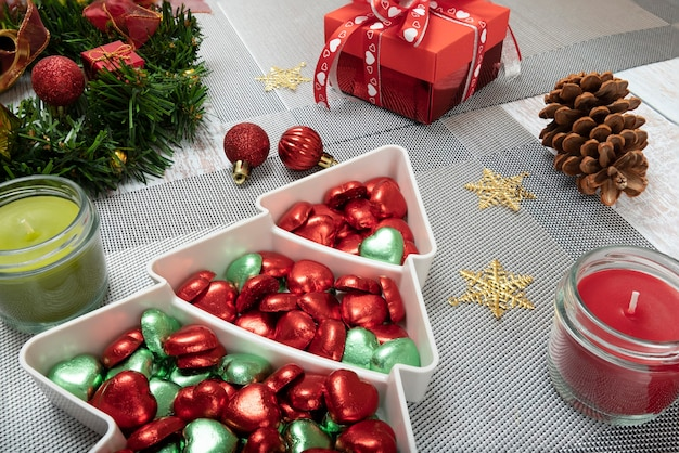 Christmas dinner table decorations with a plate of colorful chocholate candies.