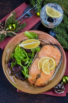 Christmas dinner table setting. delicious salmon steak grilled on plate with lemon and assorted salad on dark stone table . top view, copy space
