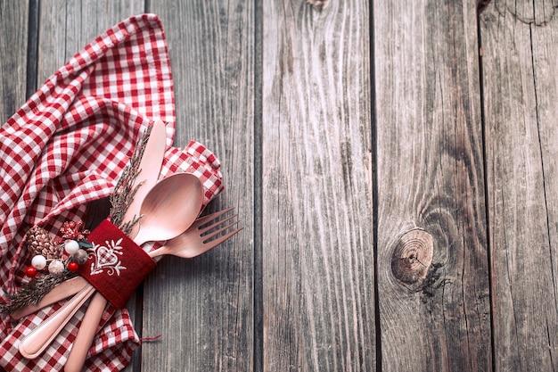 木製の背景、お祝いのコンセプト、家庭的な雰囲気の美しいカトラリーやお祝いデコレーションでクリスマスディナー