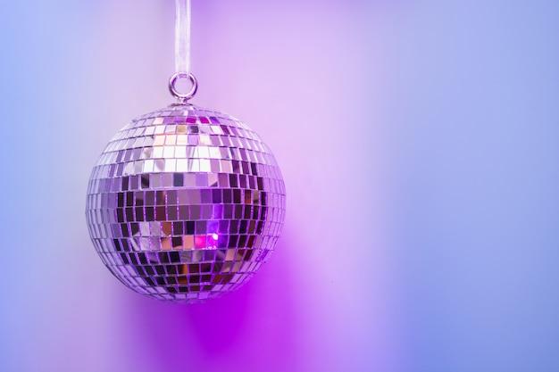Christmas disco ball on neon pink and blue.