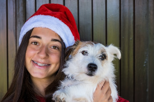 여자와 크리스마스 개입니다. 행복한 순간, 크리스마스 모자를 쓴 웃는 얼굴.